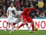 Jonathan de Guzman attempts to challenge Luis Suarez for the ball on November 25, 2012