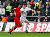 Raheem Sterling tugs the shirt of Ben Davies as they chase the ball on November 25, 2012