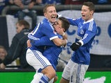 Schalke teammates Lewis Holtby and Julian Draxler congratulates goalscorer Klaas-Jan Huntelaar on November 24, 2012