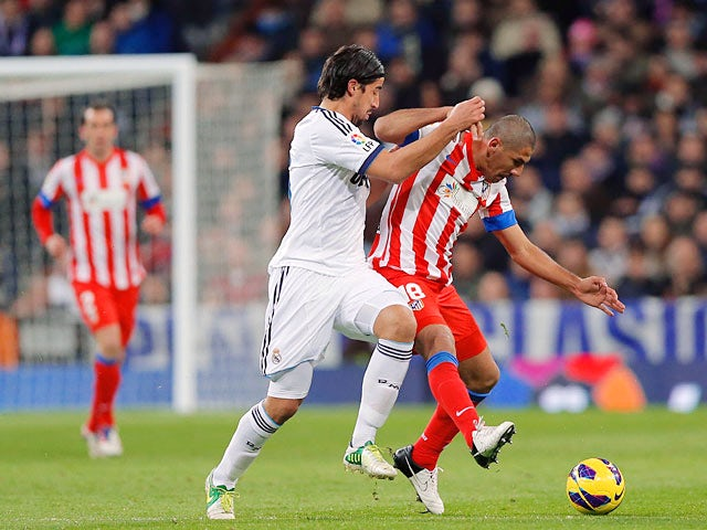 Real Madrid's Sami Khedira and Atletico Madrid's Cata Diaz battle for the ball on December 1, 2012
