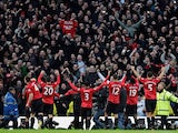 Manchester United players celebrate with fans after beating rivals Manchester City on December 9, 2012