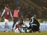 Aston Villa striker Darren Bent is treated for injury at Carrow Road on December 11, 2012