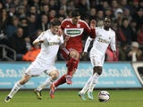 Middlesbrough's Emmanuel Ledesma battles for possession with two Swansea players on December 12, 2012