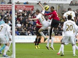 United's Patrice Evra jumps highest to open the scoring against Swansea on December 23, 2012