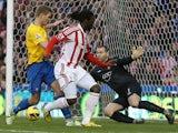 Kenwyne Jones flicks the ball past Kelvin Davis to score the equaliser on December 29, 2012