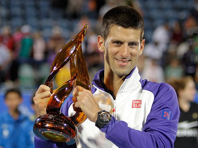 Novak Djokovic poses with the trophy after winning to defend his World Tennis Championship in Abu Dhabi on December 29, 2012