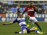 Swansea winger Wayne Routledge is tackled by Reading's Alex Pearce during the match on December 26, 2012
