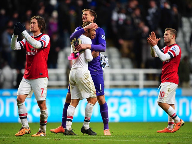 Arsenal players celebrate their win over Newcastle after the final whistle of their Premier League match on December 29, 2013