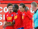 Aldershot's Guy Madjo (centre) celebrates with teammates after scoring during their match on April 17, 2012