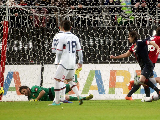 Two Genoa players look on at Daniele Conti scores Cagliari's winner in their Serie A clash on January 13, 2013