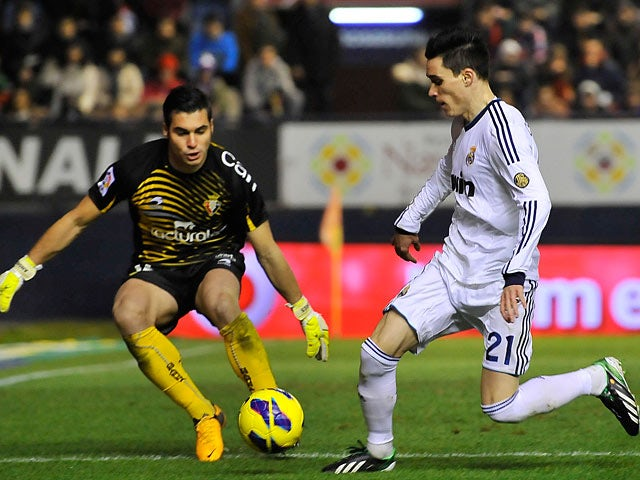Real Madrid's Jose Callejon and Osasuna's Andres Fernandez battle for the ball on January 12, 2013
