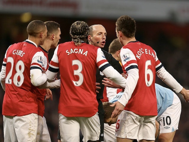 Arsenal players surround referee Mike Dean following the sending off of Laurent Koscielny against Man City on January 13, 2013