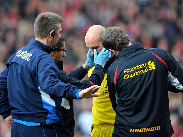 Liverpool goalkeeper Pepe Reina receives treatment after a clash with Manchester United's Shinji Kagawa on January 13, 2013
