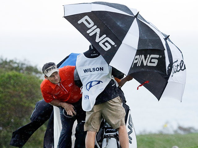 Mark Wilson and his caddy hide behind their umbrella during the windy weather in Hawaii on January 7, 2013