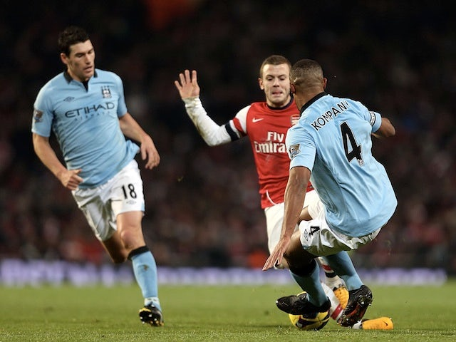 City captain Vincent Kompany tackles Arsenal's Jack Wilshere, a challenge which saw him receive a red card on January 13, 2013