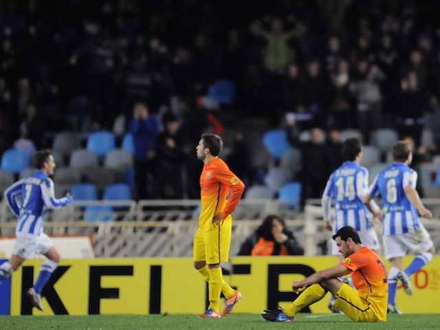 Barcelona players are dejected on the pitch following a late goal and a loss against Real Sociedad on January 19, 2013