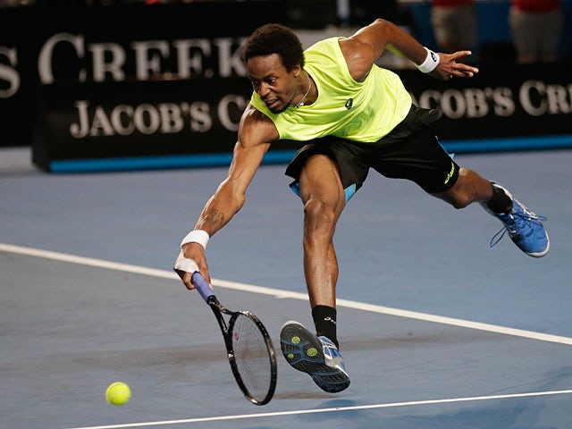 Gael Monfils reaches out for a backhand return to Gilles Simon during their third round match at the Australian Open on January 19, 2013