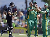 South Africa's Rory Kleinveldt is congratulated by his teammates after taking the wicket of NZ's Grant Elliot on January 19, 2013