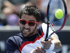 Serbia's Janko Tipsarevic plays a shot in his third round match against Julien Benneteau at the Australian Open tennis championship on January 18, 2013