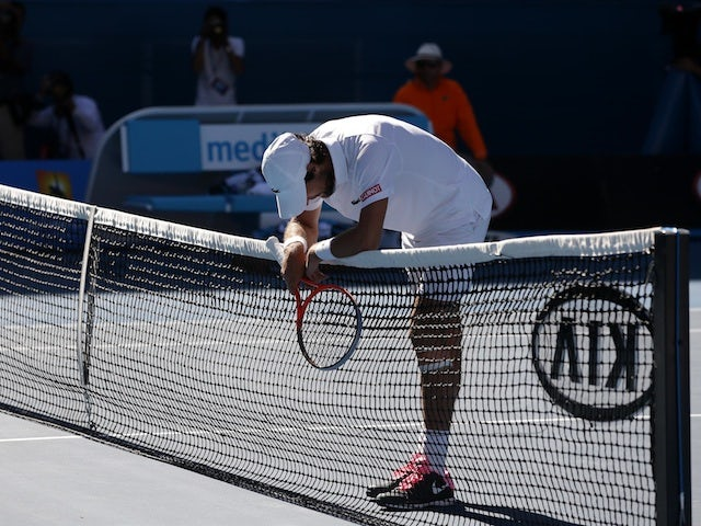 Frenchman Jeremy Chardy rests on the net following his straight-sets defeat to Andy Murray on January 23, 2013