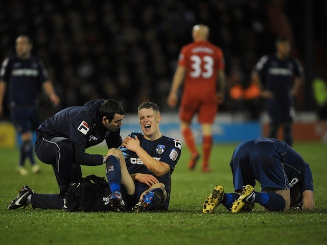 Oldham hero Matt Smith winces in pain following a shoulder injury in the game against Liverpool on January 27, 2013