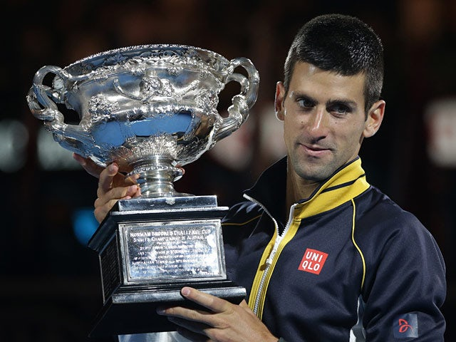 Novak Djokovic poses with the trophy after defeating Andy Murray in the men's final at the Australian Open on January 27, 2013