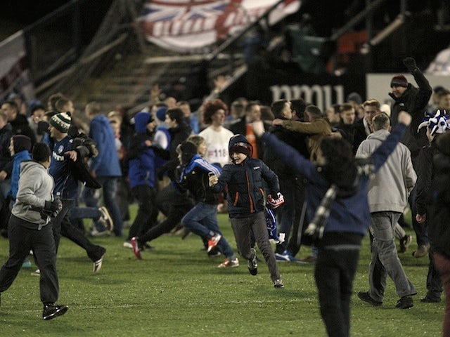 Oldham fans invade the pitch following their historic fourth round victory over Liverpool on January 27, 2013