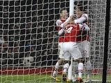 Theo Walcott is congratulated by team mates Jack Wilshere and Olivier Giroud after scoring his team's fourth goal against West Ham on January 23, 2013