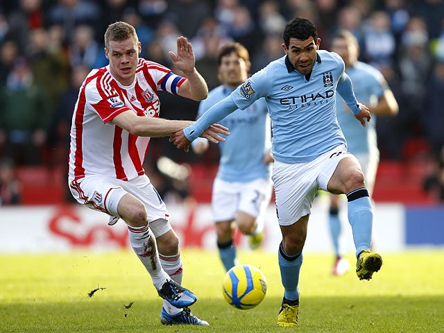 Ryan Shawcross and Carlos Tevez battle for the ball during their FA Cup fourth round tie on January 26, 2013