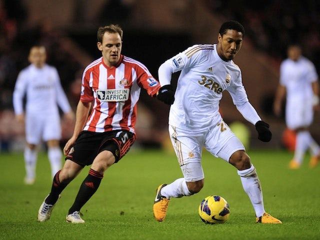 Swansea's Jonathan de Guzman shields the ball from Sunderland's David Vaughan on January 29, 2013