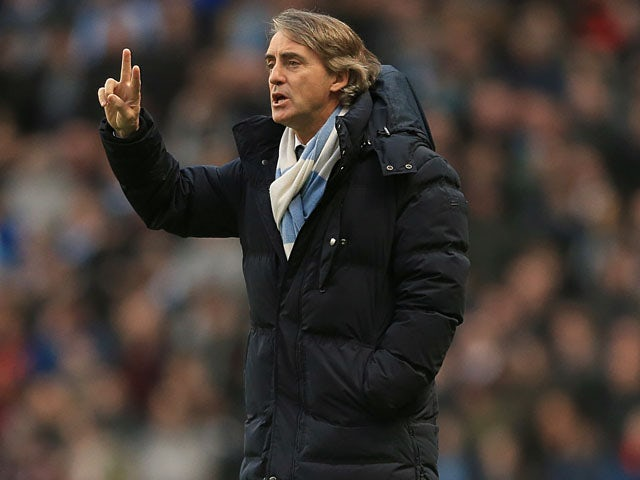 Manchester City manager Roberto Mancini gives instructions on the touchline during his side's match with Liverpool on February 3, 2013