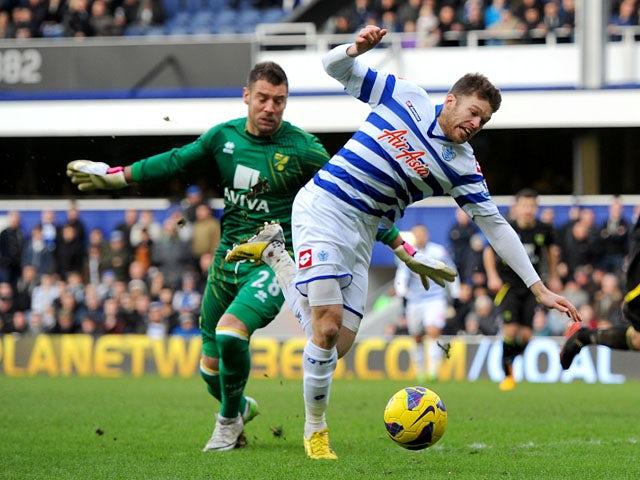 Norwich City goalkeeper Mark Bunn fouls Queens Park Rangers' Jamie Mackie during the Premier League match on February 2, 2013