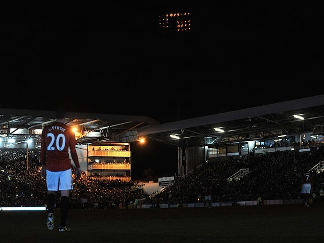 Robin Van Persie stands in the shadow of Craven Cottage after floodlight failure during the game between Fulham and Man Utd on February 2, 2013