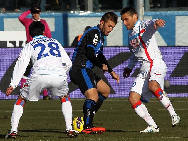 Catania's Gonzalo Ruben Bergessio and Pablo Cesar Barrientos defend against Atalanta's Michele Canini on February 10, 2013