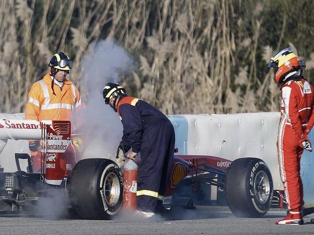 Ferrari development Pedro de la Rosa watches track marshals tend to his car after a fire on February 8, 2013