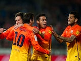 Barcelona's Lionel Messi is congratulated by team mates after scoring his second goal against Granada on February 16, 2013