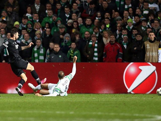 Juventus' Mirko Vucinic strikes the ball past Celtic defender Kelvin Wilson to score his team's third against Celtic on February 12, 2013