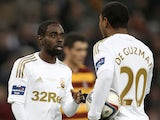 Swansea players Nathan Dyer and Jonathan de Guzman discuss who is to take the penalty after one is awarded in the game with Bradford on February 24, 2013