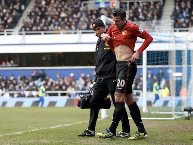 United's Robin Van Persie leaves the field, after being injured in the game with QPR on February 23, 2013