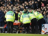 Spurs' Emmanuel Adebayor is stretched off injured during the game with Arsenal on March 3, 2013