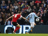 Manchester City's Carlos Tevez scores his side's first goal in their match against Barnsley on March 9, 2013