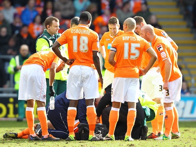 Blackpool's Barry Ferguson is treated after clattering into a teammate on March 16, 2013