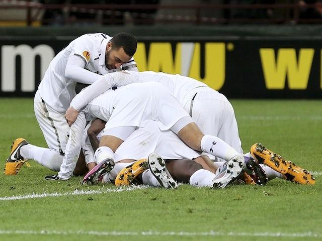 Spurs' Emmanuel Adebayor is bundled by his teammates after a goal against Inter on March 14, 2013