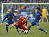 Spain's Andres Iniesta is challenged by two French players on March 26, 2013