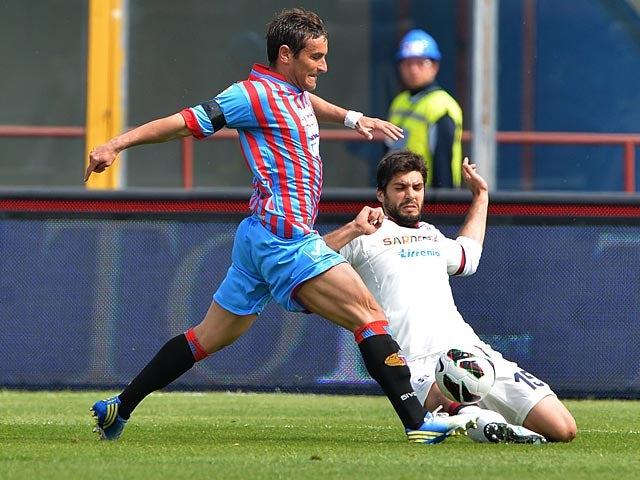 Catania's Gonzalo Bergessio and Cagliari's Luca Rossettini battle for the ball on April 7, 2013