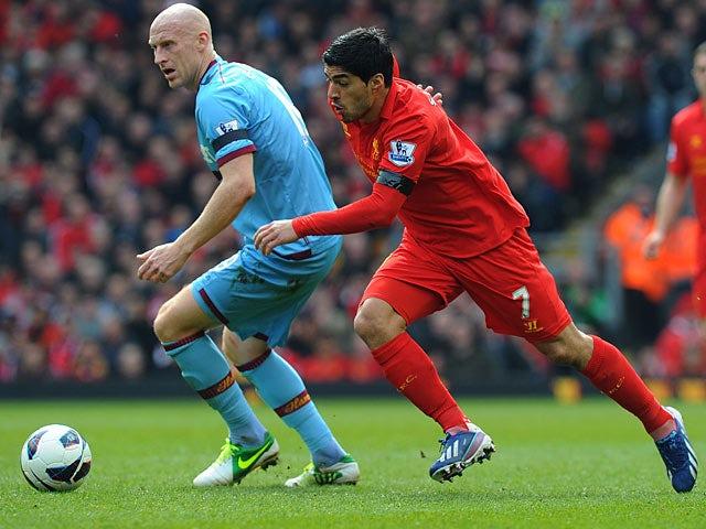 Luis Suarez skips past defender James Collins on April 7, 2013