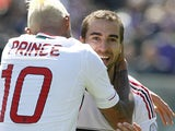 AC Milan's Mathieu Flamini is congratulated by team mates Kevin Prince Boateng after scoring his team's second against Fiorentina on April 7, 2013