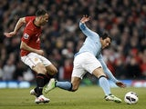 Carlos Tevez and Ryan Giggs battle for possession during the Manchester Derby on April 8, 2013
