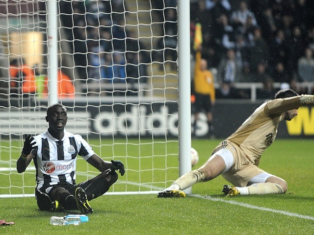 Newcastle striker Papiss Cisse sits dejected after a goal is disallowed against Benfica on April 11, 2013