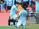 City striker Sergio Aguero celebrates a goal against Chelsea with Samir Nasri on April 14, 2013